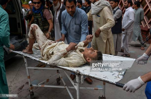 Volunteers carry an injured man on a stretcher to a hospital, following a bomb blast in Haska Mina district of Nangarhar Province on October 18,...