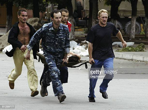 Volunteers carry an injured victim after special forces stormed a school seized by Chechen separatists on September 3 2004 in the town of Beslan...