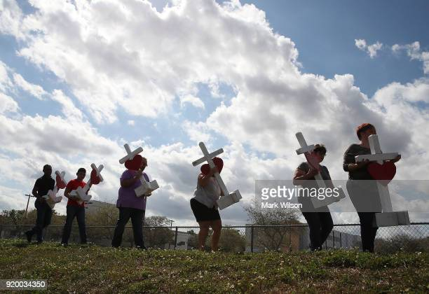 Volunteers carry crosses to be placed in front of the Marjory Stoneman Douglas High School where 17 people were killed on February 14 on February 18...