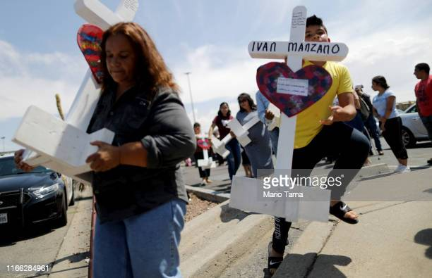 Volunteers carry handmade crosses memorializing the victims of a mass shooting to a makeshift memorial outside Walmart where the shooting took place...