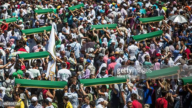 Volunteers carry some of the 136 coffins newlyidentified victims of the 1995 Srebrenica massacre to their graves during the 20th anniversary of the...
