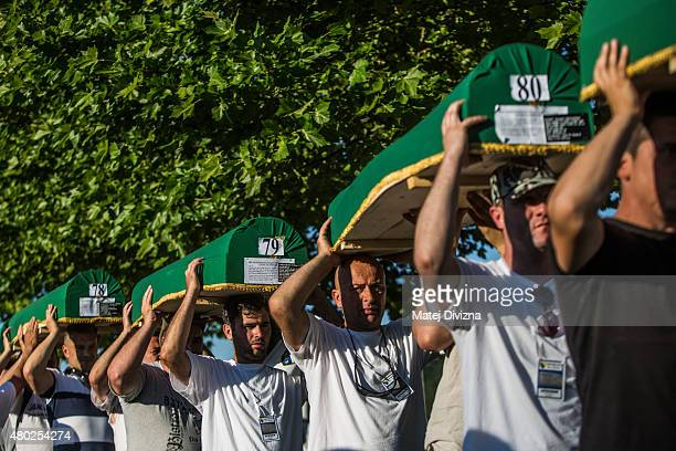 Volunteers carry some of the 136 coffins of victims of the 1995 Srebrenica massacre at the Potocari cemetery and memorial near Srebrenica on July 10...