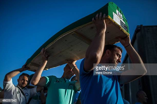 Volunteers carry some of the 136 coffins of victims of the 1995 Srebrenica massacre at the Potocari cemetery and memorial near Srebrenica on July 10,...