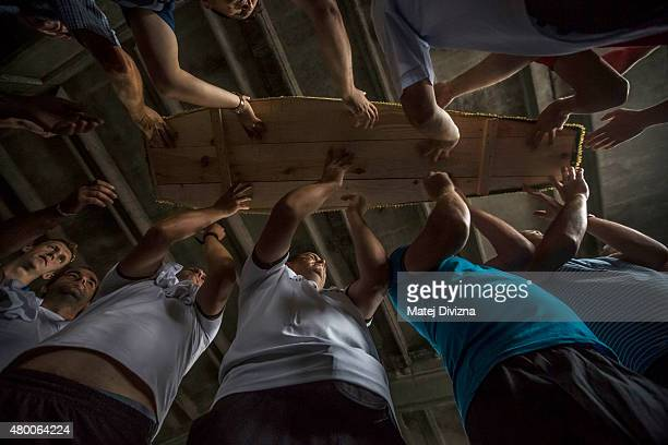 Volunteers carry some of the 136 coffins of victims of the 1995 Srebrenica massacre in the hall at the Potocari cemetery and memorial near Srebrenica...
