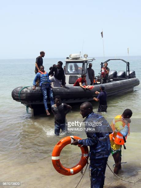 Volunteers carry the bodies of babies as migrants who survived the sinking of an inflatable dinghy boat off of the coast of Libya are brought ashore...