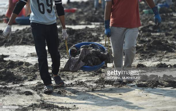 Volunteers carry trash during a clean up drive led by Indian lawyer and environmentalist Afroz Shah at the Versova beach in Mumbai on December 2 2017...