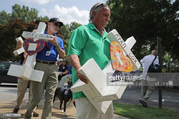 Volunteers carry wood crosses with the names of 12 shooting victims to a makeshift memorial at the Municipal Center June 02 2019 in Virginia Beach...