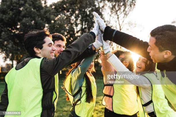 volunteers celebrating together with high five at sunset - attività foto e immagini stock