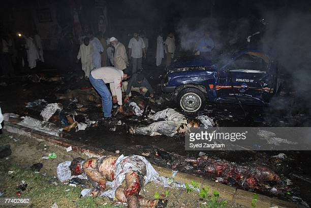 Volunteers check bodies of Pakistani people party activists laying in the street after a powerful suicide car bomb blast was set off near a vehicle...