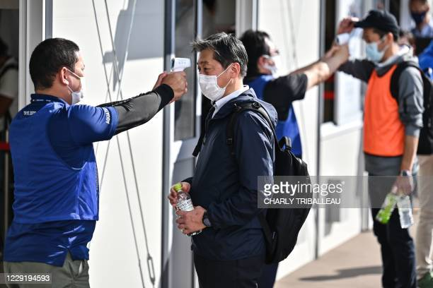 Volunteers check other volunteers acting as spectators during a test of potential spectator and games screening measures ahead of the Tokyo 2020...