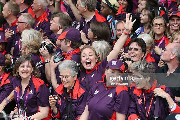 Volunteers cheer during the London 2012 Victory Parade for Team GB and Paralympic GB athletes on September 10, 2012 in London, England.