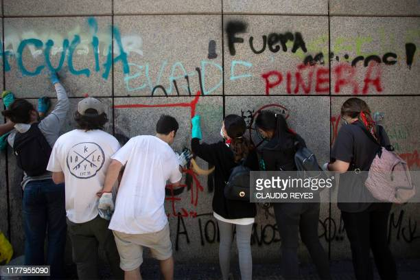 Volunteers clean a vandalised wall in Santiago after violent protests erupted over a now suspended hike in metro ticket prices on October 24 2019 The...
