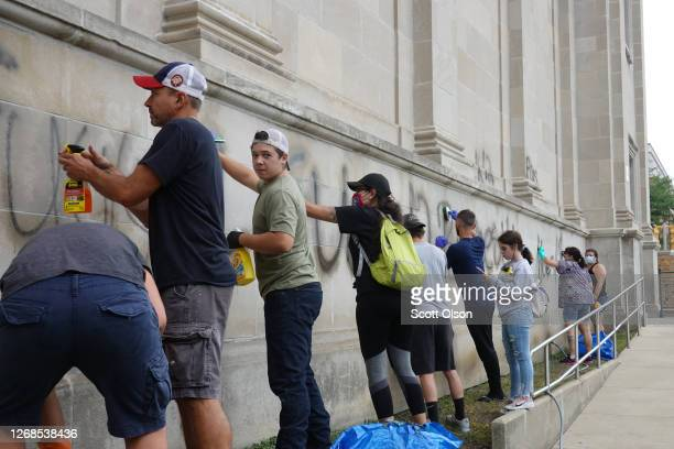 Volunteers clean graffiti from a high school near the Kenosha County Courthouse following another night of unrest on August 25, 2020 in Kenosha,...