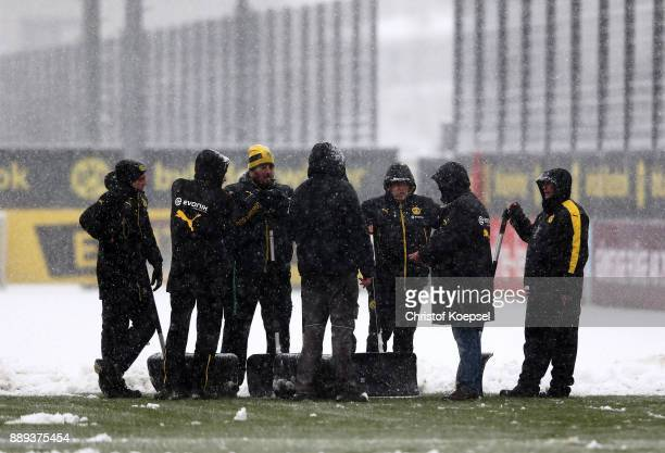 Volunteers clean off the training ground of snow prior to the cancelled training session at Brackel Training Ground Iduna Park on December 10 2017 in...