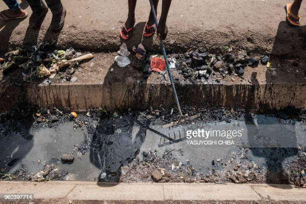 Volunteers clean the drainage during the community cleanup event supported by UN Environment at Kibera slum in Nairobi Kenya on Africa day which...