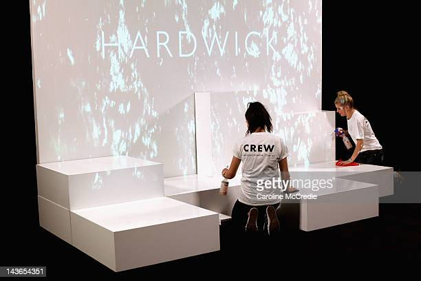 Volunteers clean the stage ahead of the Hardwick show on day three of MercedesBenz Fashion Week Australia Spring/Summer 2012/13 at Overseas Passenger...