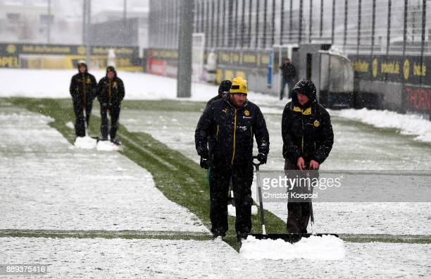 Volunteers clean the training ground of snow prior to the cancelled training session at Brackel Training Ground Iduna Park on December 10 2017 in...