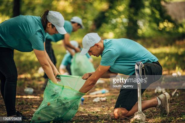 volunteers cleaning garbage - disability collection stock pictures, royalty-free photos & images