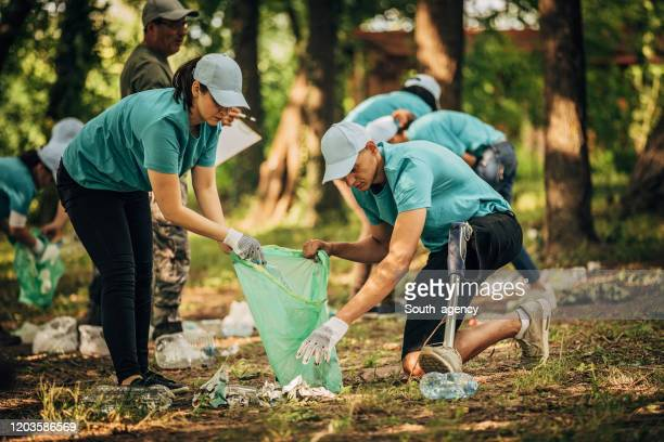 volunteers cleaning garbage together in park - disability collection stock pictures, royalty-free photos & images