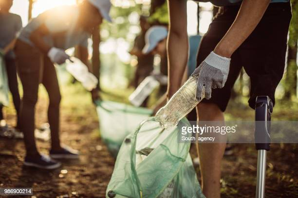 volunteers cleaning park - sustainability stock photos and pictures
