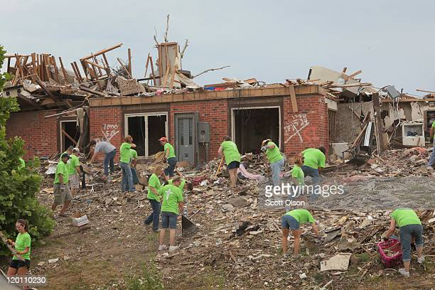 Volunteers clear debris from a tornado-damaged apartment complex July 30, 2011 in Joplin, Missouri. Joplin continues to recover from the May 22nd...