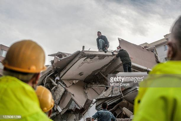 Volunteers clear rubbles as they search for survivors in a collapsed building after a strong earthquake struck the country's western coast and parts...