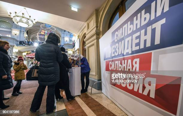 Volunteers collect signatures in support of Russian President Vladimir Putin as a candidate in March 18 presidential election at the GUM department...