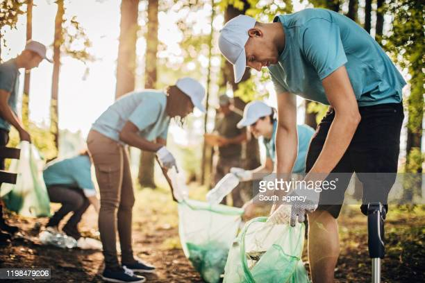 volunteers collecting garbage in park area - disability collection stock pictures, royalty-free photos & images