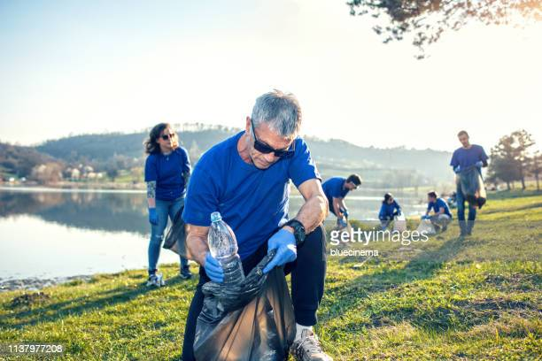 volunteers collecting garbage - social responsibility stock pictures, royalty-free photos & images