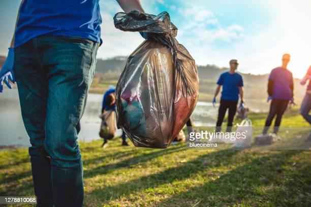 vrijwilligers die huisvuil verzamelen - onderste deel stockfoto's en -beelden