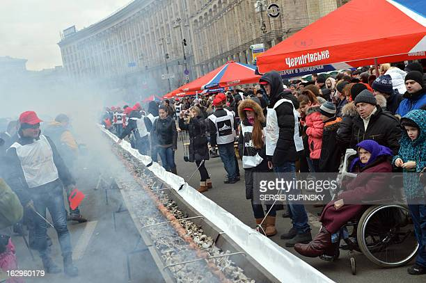 Volunteers cook a shashlyk or skewer of meat measuring 1506 meters in length in the Ukrainian capital of Kiev to set a new world record on March 2...