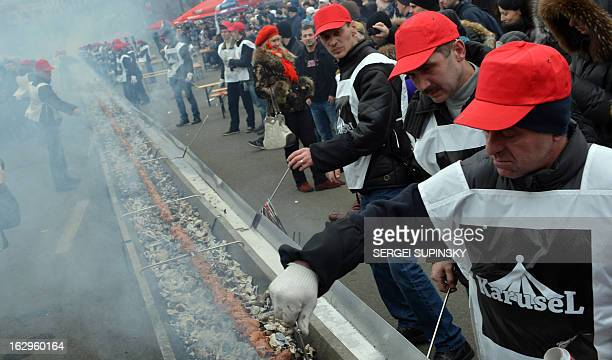 Volunteers cook shashlyk or a skewer of meat measuring 1506 meters in length in the Ukrainian capital of Kiev to set a new world record on March 2...