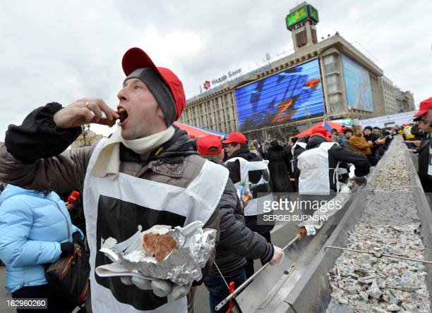 A volunteers cook tastes a piece of shashlyk or skewered meat which was cooked in a huge brazier in the Ukrainian capital of Kiev on March 2 2013 to...
