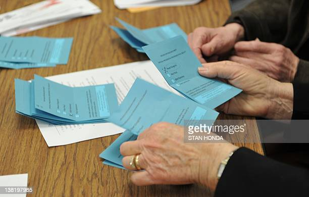 Volunteers count ballots from voters during a Republican caucus at Becker Middle School February 4 2012 in Las Vegas Nevada AFP PHOTO/Stan HONDA