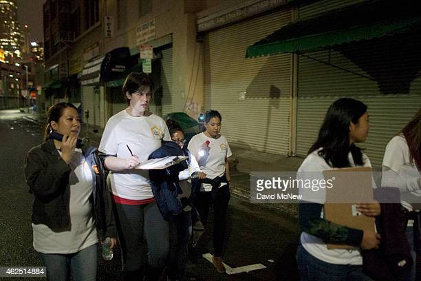 Volunteers count homeless people on a dark street on Skid Row during the 2015 Greater Los Angeles Homeless Count conducted by the Los Angeles...