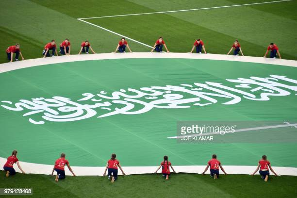 Volunteers deploy Saudi Arabia's giant flag on the pitch before the start of the Russia 2018 World Cup Group A football match between Uruguay and...
