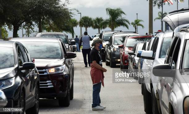 Volunteers direct traffic as residents line up in their cars at a food distribution site at Lake-Sumter State College sponsored by the Second Harvest...