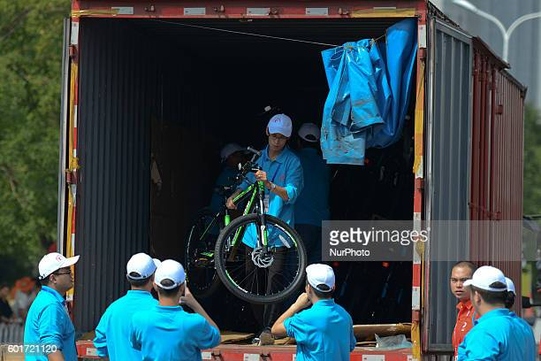 Volunteers discharge the car tranporting bikes for riders ahead of the opening stage of the 2016 Tour of China 1 Wuqing district of Tianjin the...