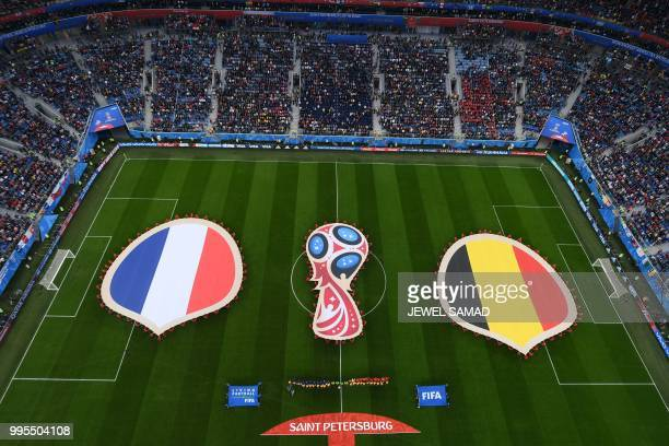 Volunteers display the French flag and the Belgian flag prior to the Russia 2018 World Cup semi-final football match between France and Belgium at...