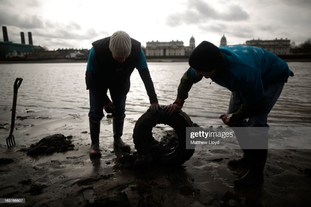 Volunteers dispose of a tyre that was buried in the banks of the River Thames on the Isle of Dogs on March 15, 2013 in London, England. The Thames21 charity leads volunteers in deep cleans of some of the Thames' most polluted and littered areas, using the annual low tides to reach areas normally impossible to access.