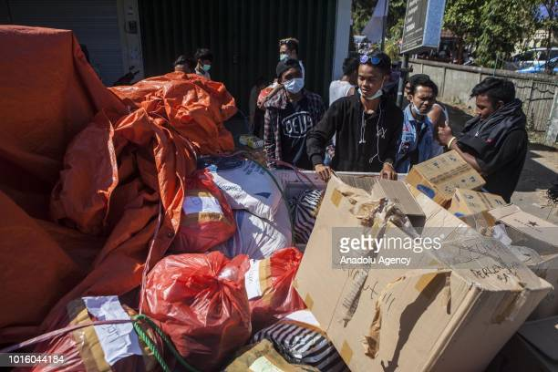 Volunteers distribute aid in the form of food and clothing at a temporary shelter in Lombok Indonesia on August 13 2018 According data from the...