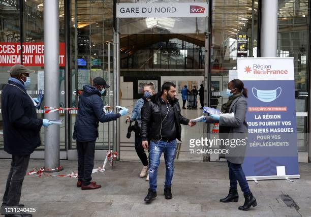 Volunteers distribute face masks and leaflets to commuters in front of the Gare du Nord train station in Paris on April 29 on the 44th day of a...
