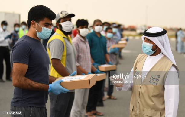 Volunteers distribute Iftar meals to migrant workers keeping distance from each other during the Muslim holy month of Ramadan within the initiative...