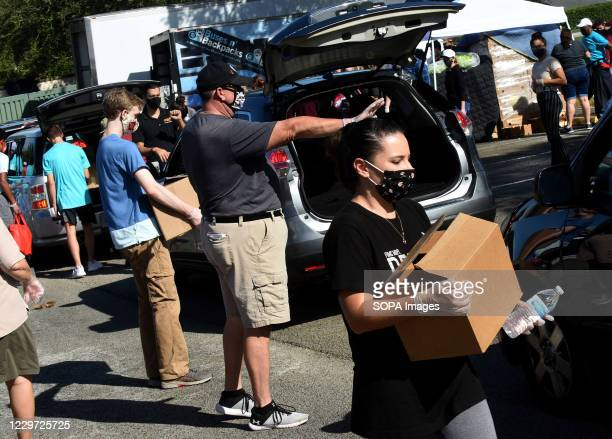 Volunteers distribute turkeys and other food assistance to the needy at a food distribution site at Lake-Sumter State College sponsored by the Second...