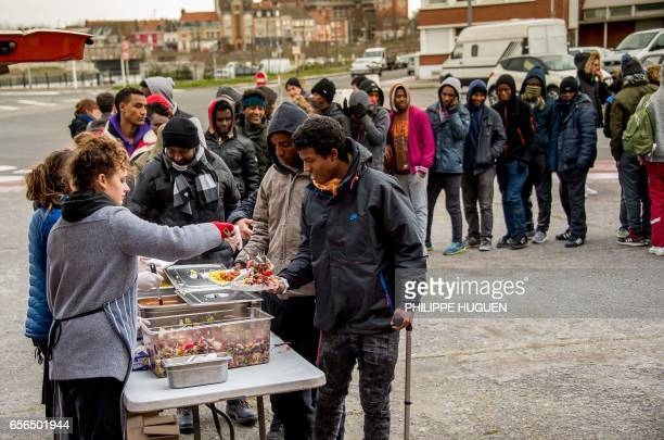 Volunteers ditribute meals to migrants on March 22 2017 as the administrative court ordered to not enforce the Calais' decrees prohibiting in certain...