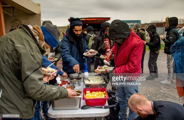 Volunteers ditribute meals to migrants on March 22 2017 in Calais as an administrative court ordered not to enforce municipal decrees prohibiting in...