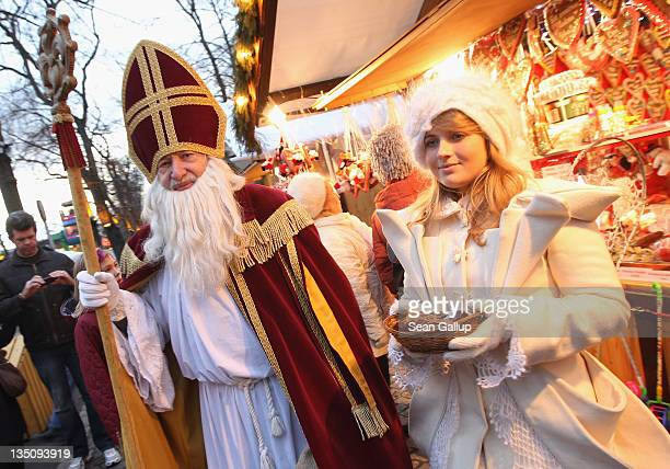 Volunteers dressed as St Nicholas and an angel distribute chocolates at the Charlottenburg Christmas market on December 6 2011 in Berlin Germany...