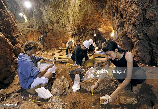 Volunteers dust the ground on August 18 in the coastal cave of Lazaret near Nice southern France where a 170000 year old forehead bone has been...