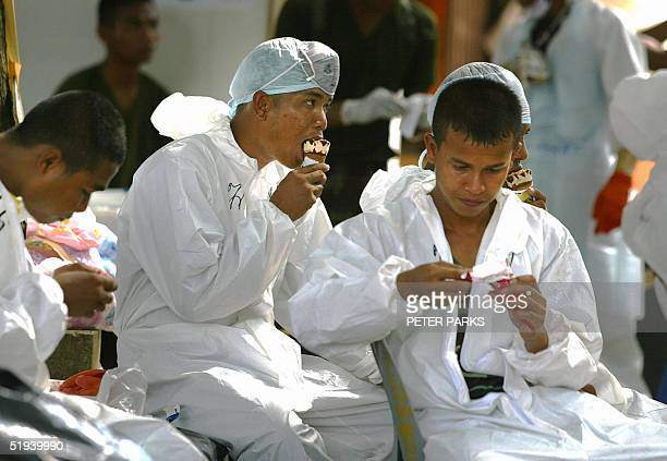 Volunteers eat icecream as they take a rest at Yan Yao Temple in Thailand's Phang Nga province 12 January 2005 where about 60 experts from around the...