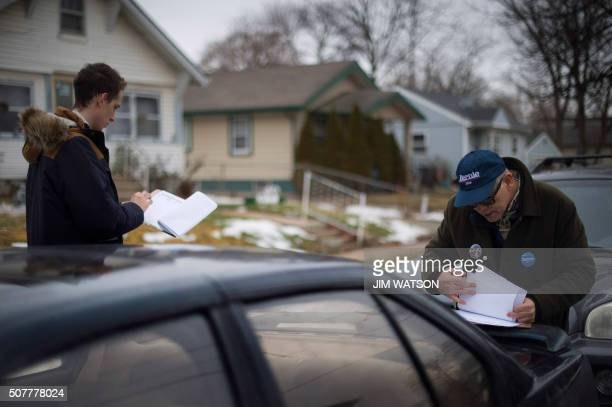 Volunteers Fergus Wilson and Bob Swope look over their address lists as they begin a morning of voter canvassing for Democratic presidential...